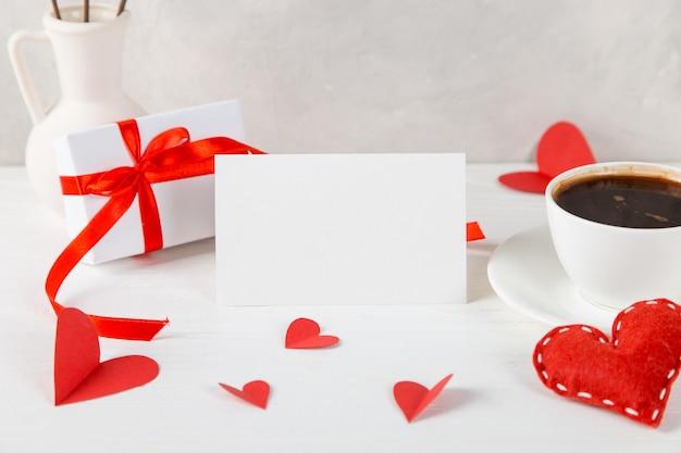 Eine vase mit baumwolle, rotem herzen, morgenkaffee und einem geschenk gegen die einer hellen wand, konzept, eine postkarte für valentinstag.