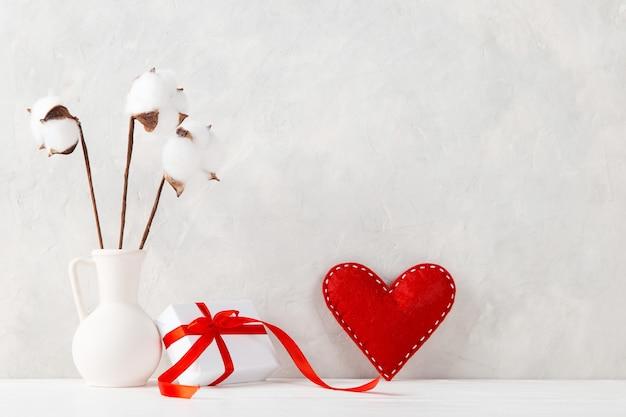Eine vase mit baumwolle, rotem herzen und einem geschenk gegen die einer hellen wand, ein konzept, eine postkarte zum valentinstag.