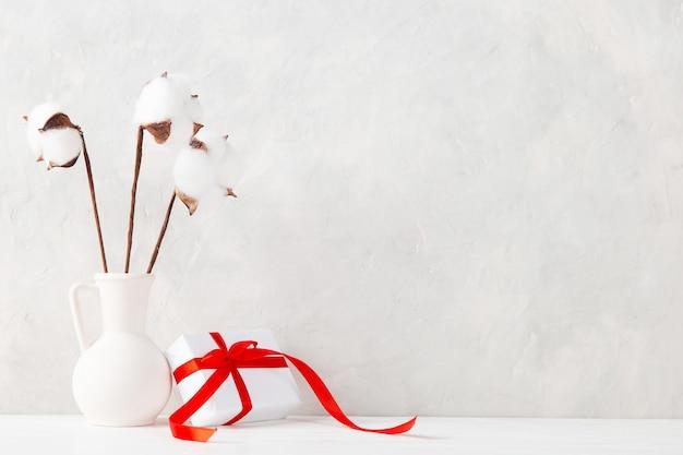 Eine vase mit baumwolle und ein geschenk gegen die einer hellen wand, ein konzept, eine postkarte zum valentinstag.