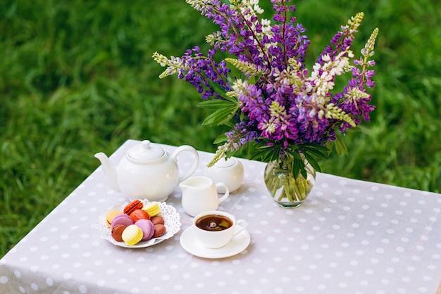 Eine vase mit lupinenblüten, eine teekanne und eine tasse tee und makronen auf dem tisch.