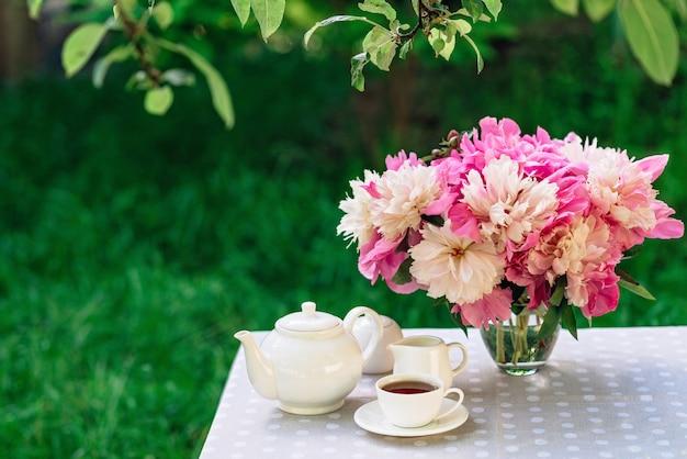 Eine vase mit pfingstrosen blüht in der nähe einer tasse kaffee