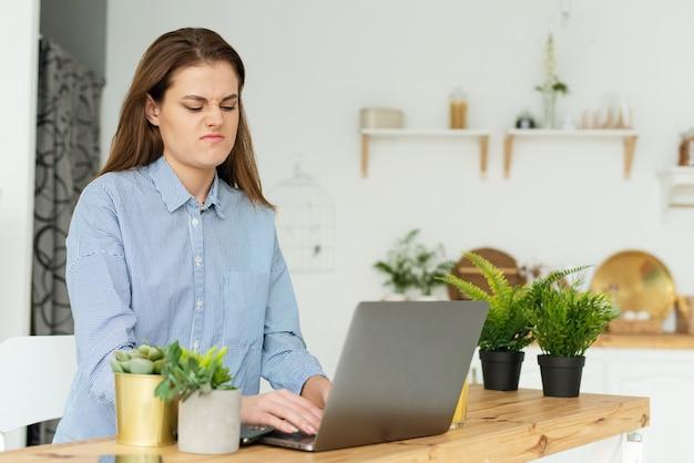 Eine verärgerte frau arbeitet zu hause mit einem laptop und ärgert sich über eine schlechte internetverbindung, verlangsamt den computer.
