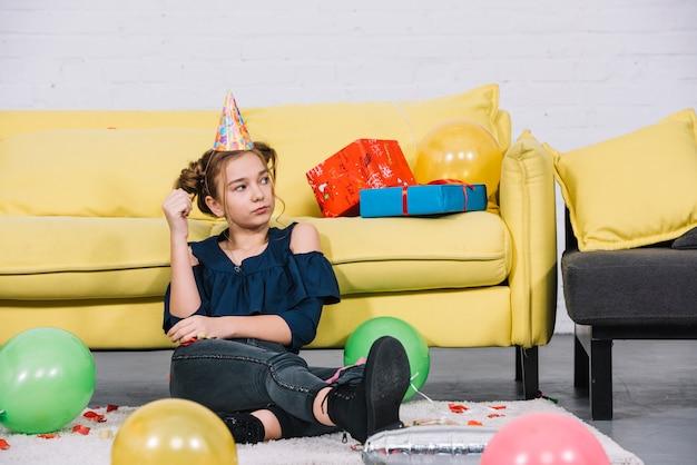 Eine verärgerte jugendliche, die zu hause auf dem weißen teppich mit ballonen sitzt