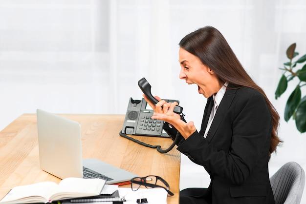 Eine verärgerte junge geschäftsfrau, die auf dem stuhl schreit am telefon sitzt