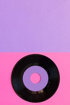 Eine veraltete vinylplatte auf einem zwei-tonnen-papierhintergrund: rosa und violett, popkultur.