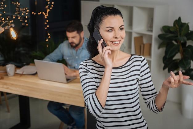 Eine vereinbarung treffen. freudige kluge positive frau, die in der mitte des büroraums steht und am telefon spricht, während sie eine vereinbarung für ihren chef trifft