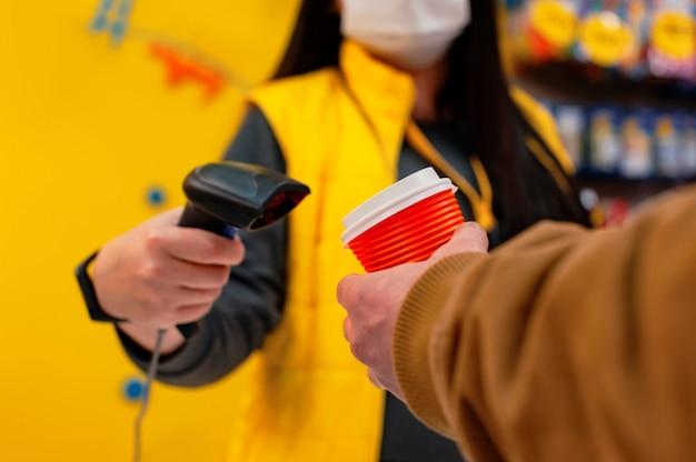 Eine verkäuferin in einer medizinischen maske eines virus hält einen barcode-scanner in den händen. ein mann mit einem glas kaffee in der hand zahlt an der kasse