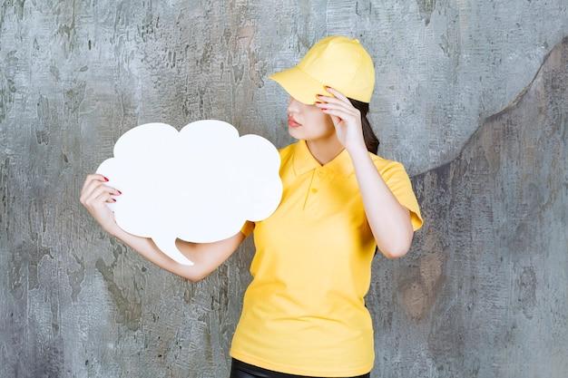 Eine verkäuferin in gelber uniform, die eine infotafel in wolkenform hält und verwirrt und verängstigt aussieht