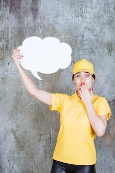 Eine verkäuferin in gelber uniform, die eine infotafel in wolkenform hält und verwirrt und verängstigt aussieht.