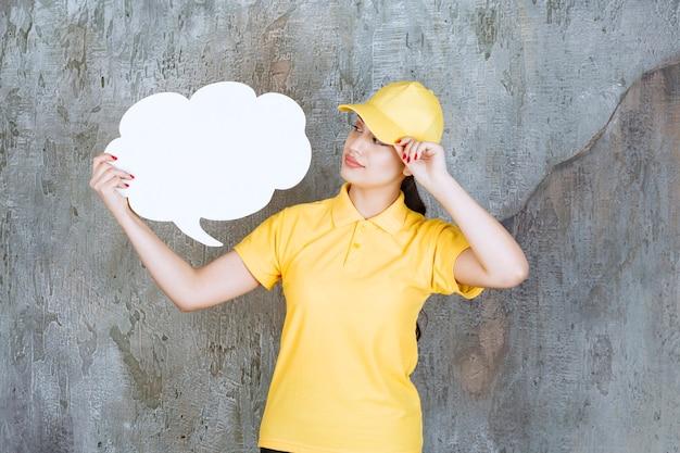 Eine verkäuferin in gelber uniform, die eine infotafel in wolkenform hält.