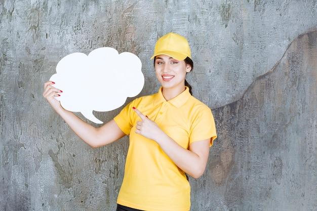 Eine verkäuferin in gelber uniform, die eine infotafel in wolkenform hält