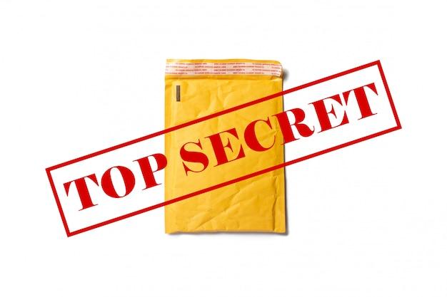 Eine versandpapiertüte für briefe oder kleine pakete mit streng geheimem text auf einem hellen raum. streng geheime informationen. flache lage, draufsicht