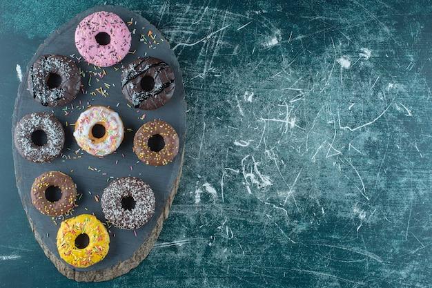 Eine verschiedene donuts auf einem brett, auf blauem hintergrund. foto in hoher qualität