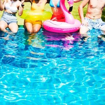 Eine verschiedene gruppe freunde, die sommerzeit am pool mit aufblasbaren hin- und herbewegungen genießen