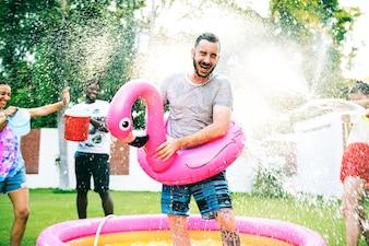 Eine verschiedene Gruppe Freunde, die Sommerzeit genießen und Wasser spritzen