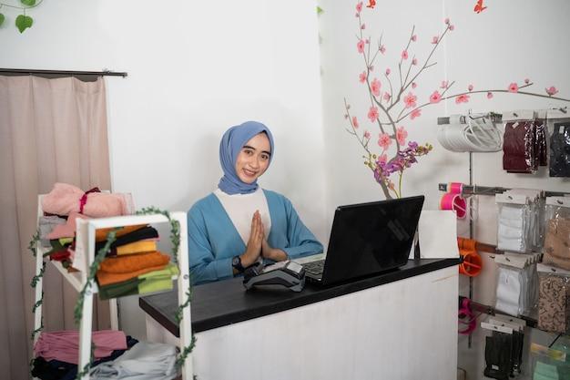 Eine verschleierte geschäftsfrau lächelt mit einer grußgeste, während sie vor einem laptop sitzt...