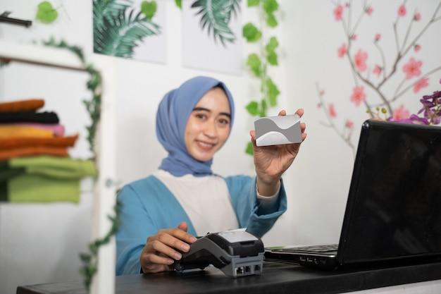 Eine verschleierte geschäftsfrau lächelt, während sie eine kreditkarte und ein elektronisches datenerfassungsgerät hält.