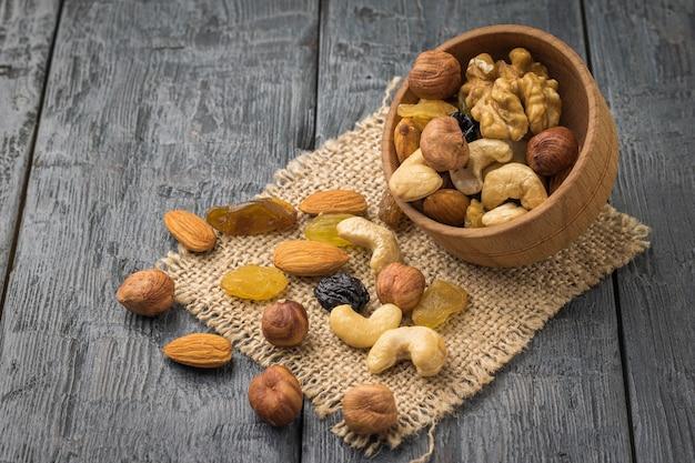Eine verschüttete mischung aus nüssen und getrockneten früchten auf einem stück sackleinen auf einem holztisch. natürliches gesundes vegetarisches essen.