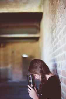 Eine vertikale aufnahme einer frau, die beim beten die bibel in der nähe ihres kopfes hält