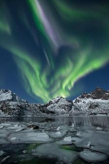 Eine vertikale aufnahme von schneebedeckten bergen unter einem schönen polarlicht in der nacht