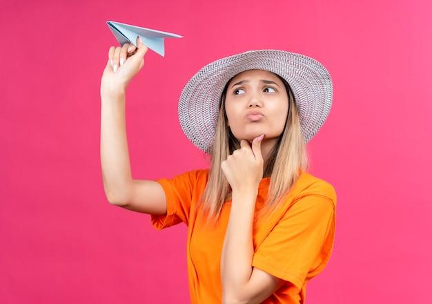 Eine verwirrte hübsche junge frau in einem orange t-shirt, das sonnenhut trägt, der mit hand auf kinn fliegendem papierflugzeug auf einer rosa wand denkt