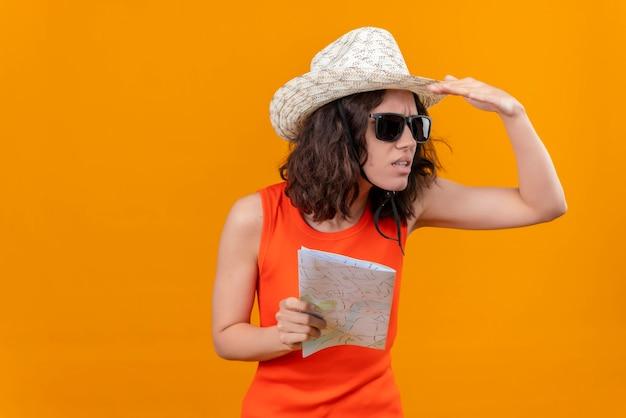 Eine verwirrte junge frau mit kurzen haaren in einem orangefarbenen hemd, das sonnenhut und sonnenbrille hält karte, die weit weg schaut