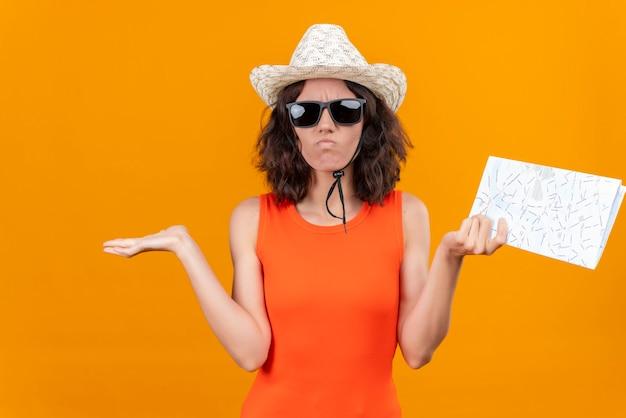 Eine verwirrte junge frau mit kurzen haaren in einem orangefarbenen hemd, das sonnenhut und sonnenbrille trägt, die hände mit karte heben, die nicht wissen, was zu tun ist