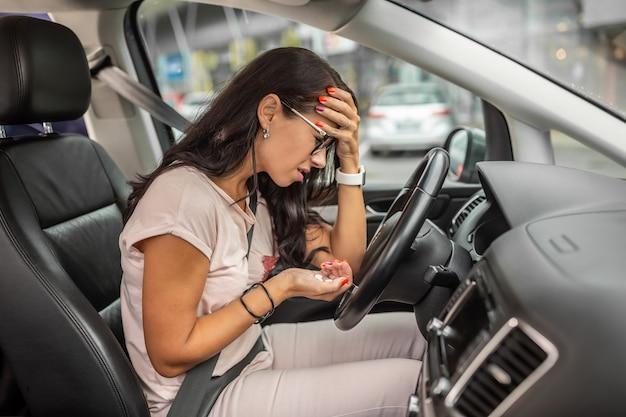 Eine verzweifelte frau hält ihren kopf auf dem fahrersitz sitzend mit einer handvoll pillen in der anderen hand.
