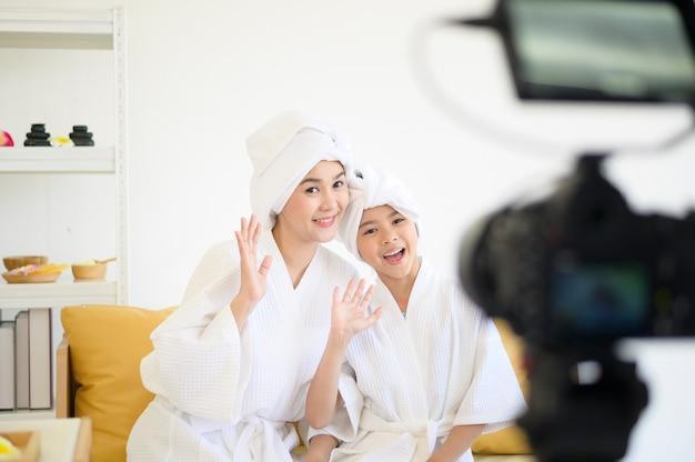 Eine videokamera, die glückliche mutter und tochter im weißen bademantel filmt