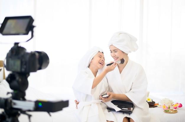 Eine videokamera, die glückliche mutter und tochter im weißen bademantel schauspielern schauspielert
