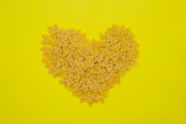Eine vielzahl von arten und formen italienischer pasta. makkaroni-produkte sind in form eines herzens verstreut.