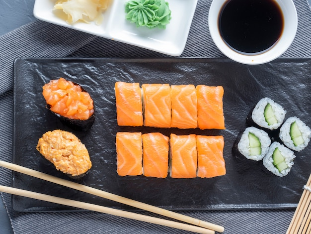 Eine vielzahl von brötchen und sushi gunkan auf einem schwarzen teller verschachtelt. daneben sind bambus-wasabi-sticks und sauce. draufsicht, flach liegen. traditionelle japanische küche