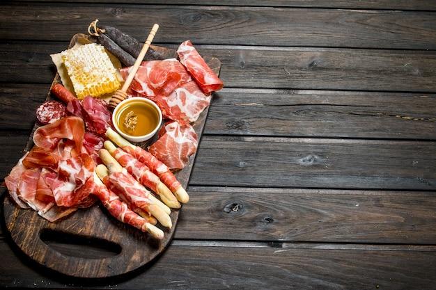 Eine vielzahl von fleischsnacks auf einem rustikalen tisch.