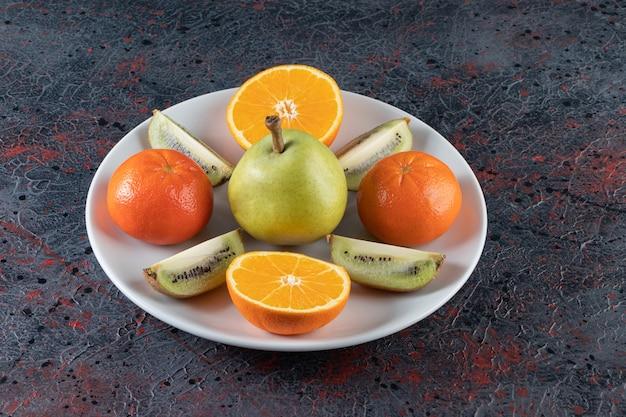 Eine vielzahl von früchten auf einem teller auf der gemischten oberfläche