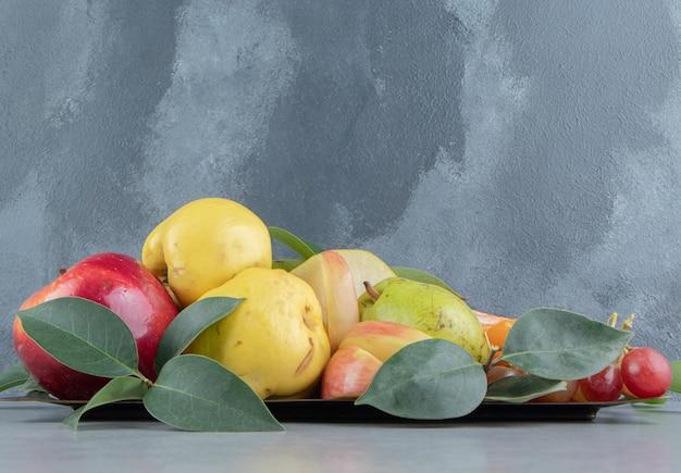 Eine vielzahl von früchten auf marmor gebündelt