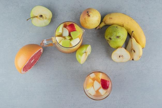 Eine vielzahl von früchten und ein glas saft auf dem marmorhintergrund. hochwertiges foto