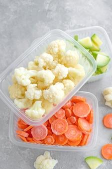 Eine vielzahl von gefrorenem gemüse in plastikbehältern auf grauem betonhintergrund gesundes essen