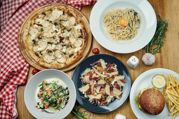 Eine vielzahl von gerichten zum mittagessen - pizza, pasta carbonara, hamburger, gedünstetes gemüse und salat mit jamon.