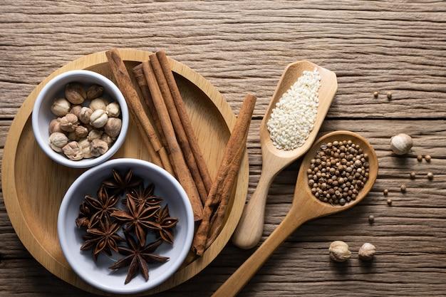 Eine vielzahl von gewürzen und natürlichen kräutern ergänzt gesunde lebensmittel auf rustikalem tisch.