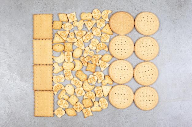 Eine vielzahl von keksen ordentlich auf marmoroberfläche aufgereiht