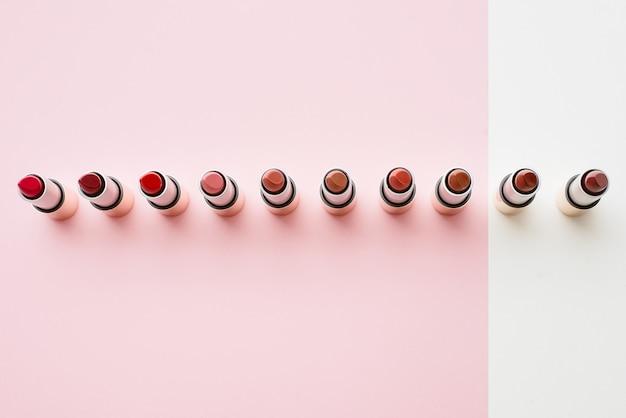 Eine vielzahl von lippenstiften ist auf pastellrosa und beige hintergründen aufgereiht. lippenstifte werden in der linie aufgereiht.