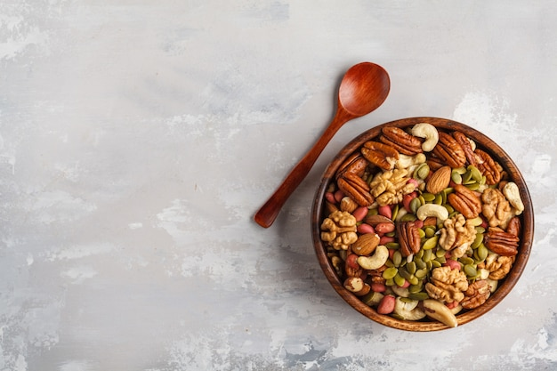 Eine vielzahl von nüssen und samen in einer holzschale, lebensmittelhintergrund, veganes gesundes lebensmittelkonzept. speicherplatz kopieren, draufsicht.
