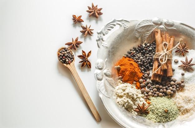 Eine vielzahl von orientalischen gewürzen auf einem schönen teller, lokalisiert auf weißem hintergrund, konzept von scharfem essen und gewürzen