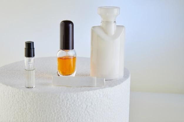 Eine vielzahl von rohlingen für handcreme, parfümerie, duschgel, flaschen ohne etikett auf einem weißen runden podium