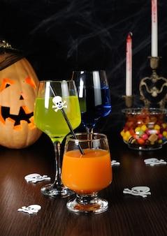 Eine vielzahl von säften und getränken auf dem tisch zu ehren von halloween