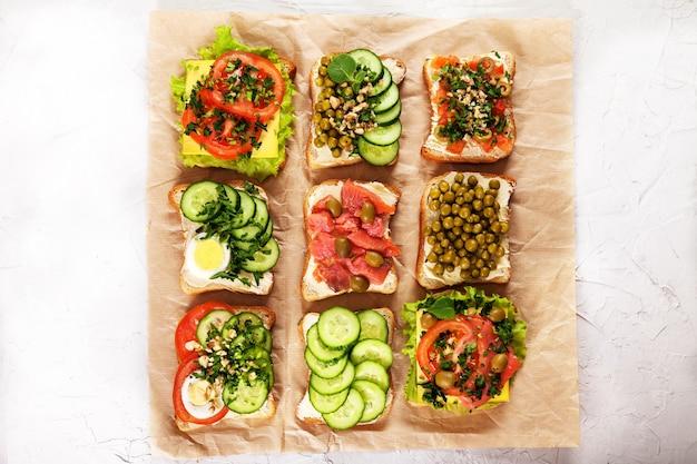 Eine vielzahl von sandwiches mit frischkäse, lachs, ei, kräutern und gemüse auf bastelpapier