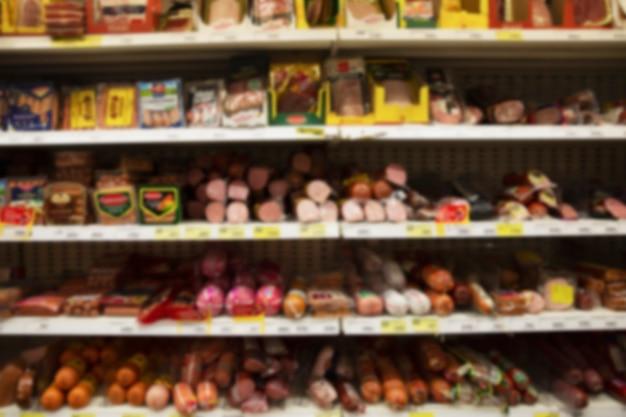 Eine vielzahl von würstchen in den regalen im supermarkt. vorderansicht. verschwommen.