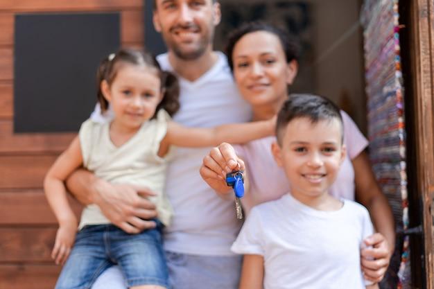 Eine vierköpfige familie, die sommerferien genießt und in den ferien ihr zuhause genießt, zieht in ein hölzernes sommerhaus, mama hält die schlüssel zum haus, die schlüssel im vordergrund