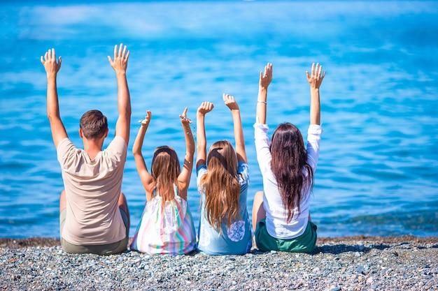 Eine vierköpfige familie hat gemeinsam spaß im strandurlaub
