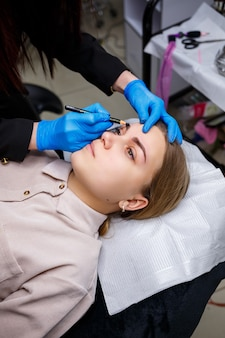 Eine visagistin bringt mit einem augenbrauenstift eine skizze auf die augenbrauen eines jungen mädchens an. professionelles make-up und kosmetische hautpflege.